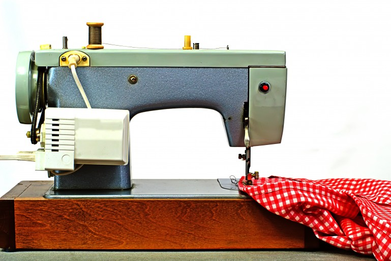 Retro symaskine. En gammel symaskine der syr i rød ternet stof